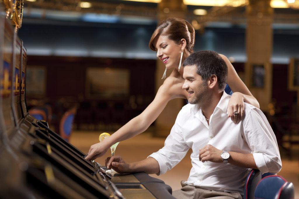 elegant couple playing slot machine in casino
